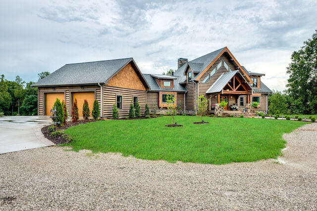 Photo of large log home with double a-frame front entrance covered porch and front porch extending the entire length of the front of the home. Stone front steps and pillars support the porch roof. the home is log chink style.
