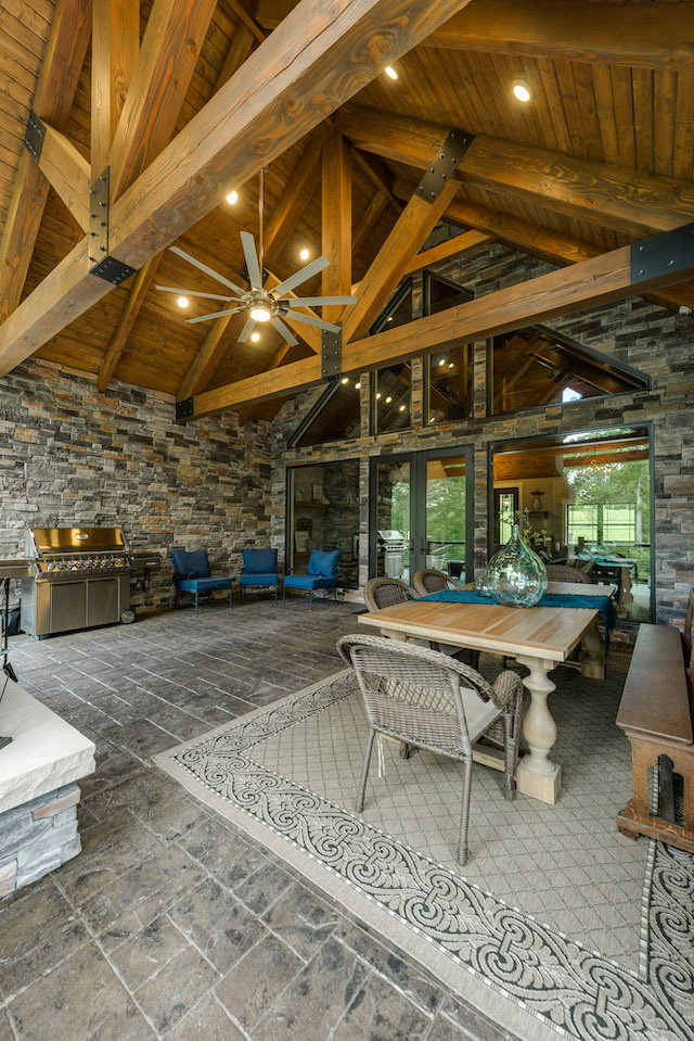 photo of porch with a-frame beams and wood ceiling and stone floor. Walls of stone and ceiling fans make the outdoor dining space luxurious
