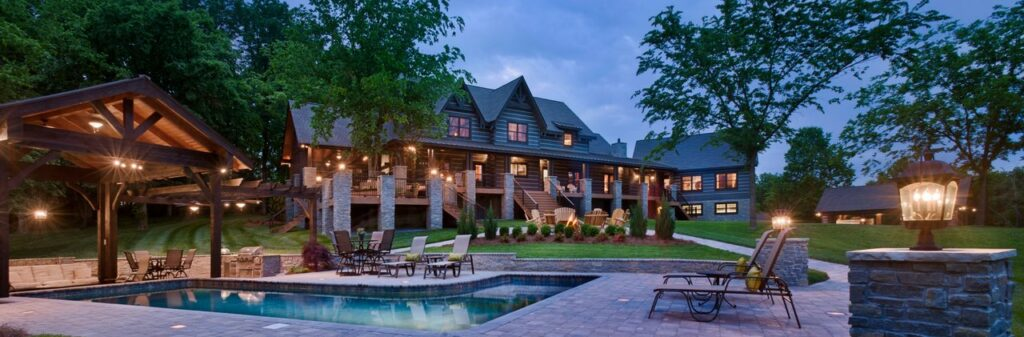 Photo of large estate log home. This photo is taken at dusk from the inground l-shaped pool with gazebo toward the back of the home. The two story raised home is accessed through a grand wood staircase leading to a porch that extends the entire length of the home. The upper floor has a series of gables. the far side of the home has an attached two story garage with a living quarters upstairs.