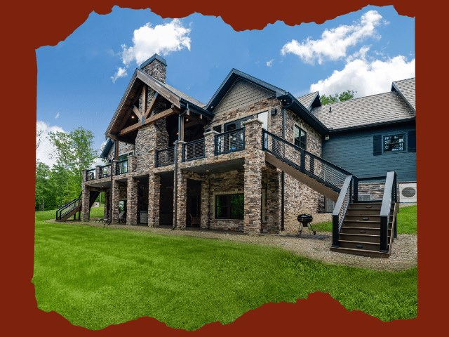 Photo of timber frame estate home with ground level patio and upper outdoor living space with expansive deck and covered porch area.