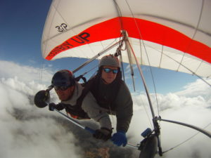 Tandem hang glider above the clouds