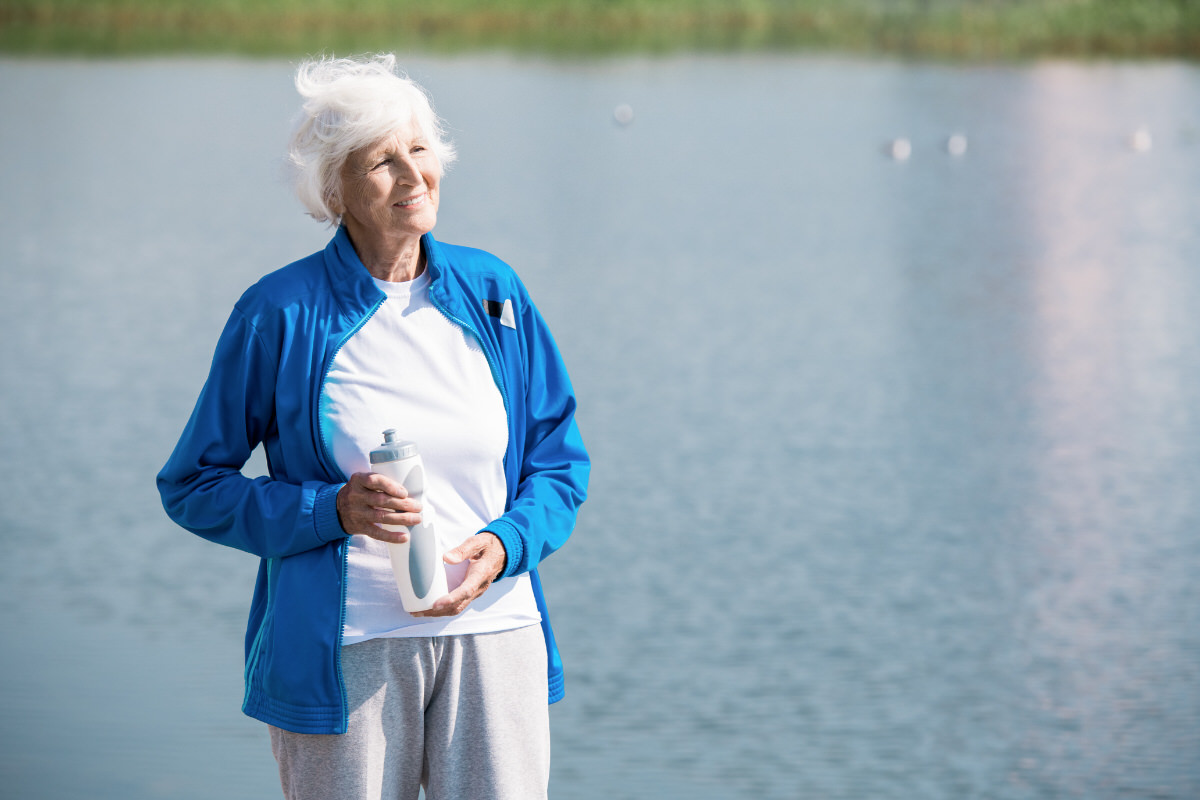 Waist up portrait of active senior woman looking away  and holding water bottle while enjoying morning run in park, copy space