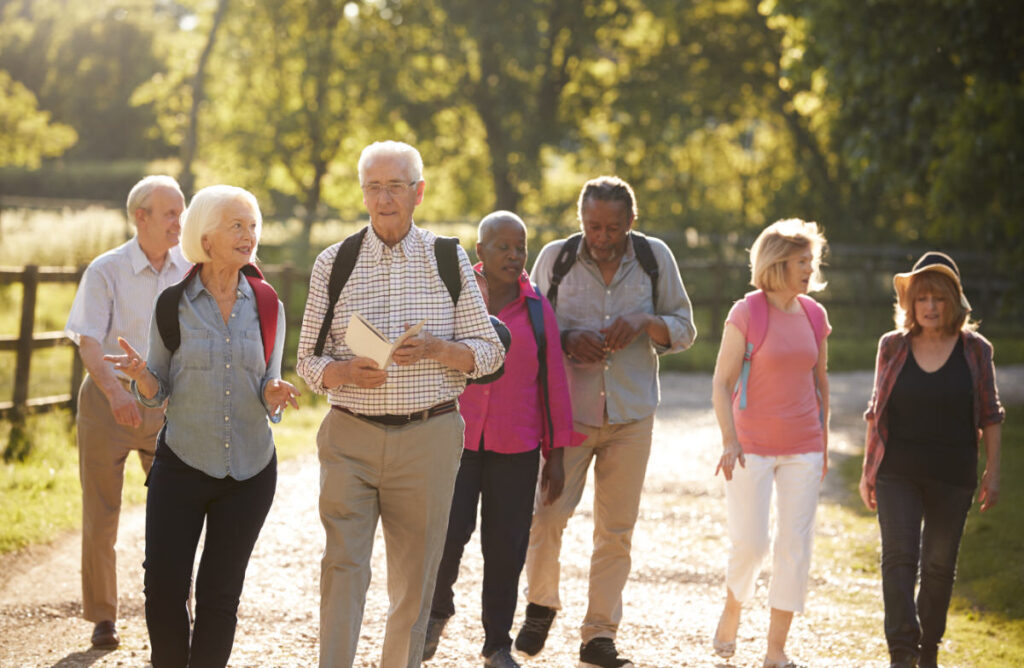 Group of Senior Friends in walking group independent retirement community walking on gravel path