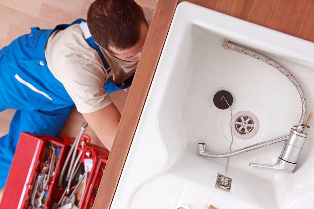 A plumber repairing clogged kitchen sink