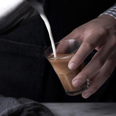 A barista pours a latte for a confence delegate.