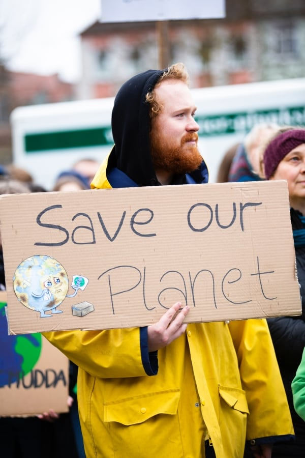 man holding a save our planet sign