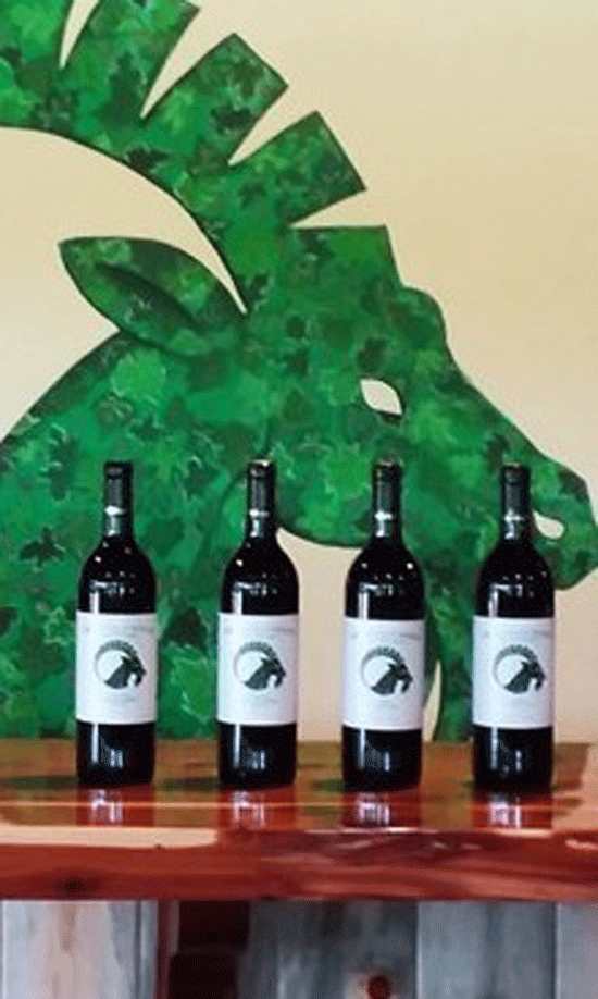 4 bottles of wine on a wood bar with a green goat logo