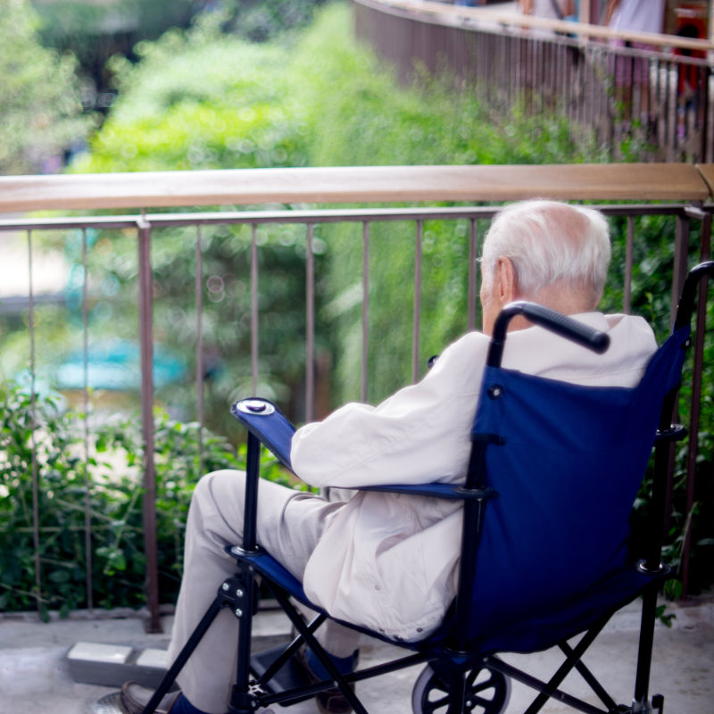 Old man in wheelchair sitting alone staring out at garden.