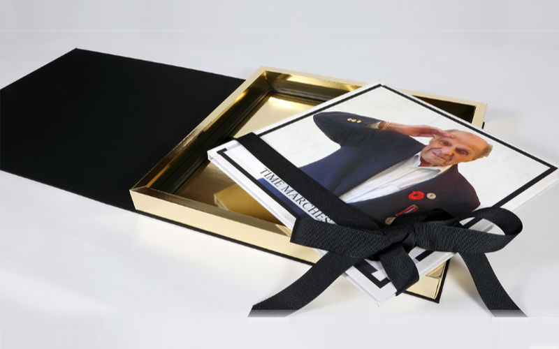 Hardcover book on top of gold trimmed box with ribbon.