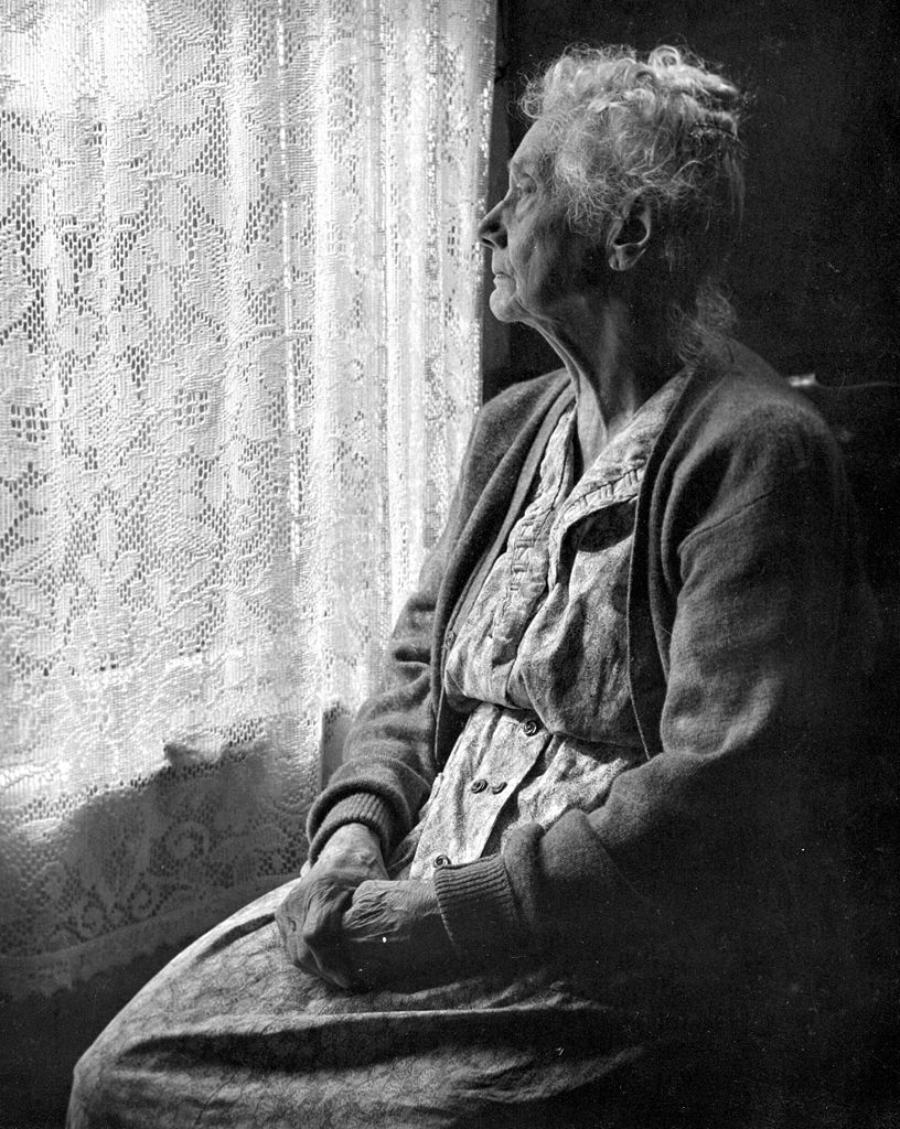 Older woman staring out window.