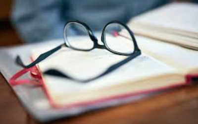 Glasses sitting on book in out of focus picture.