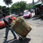 A man carrying a basket full of pineapples across a main street