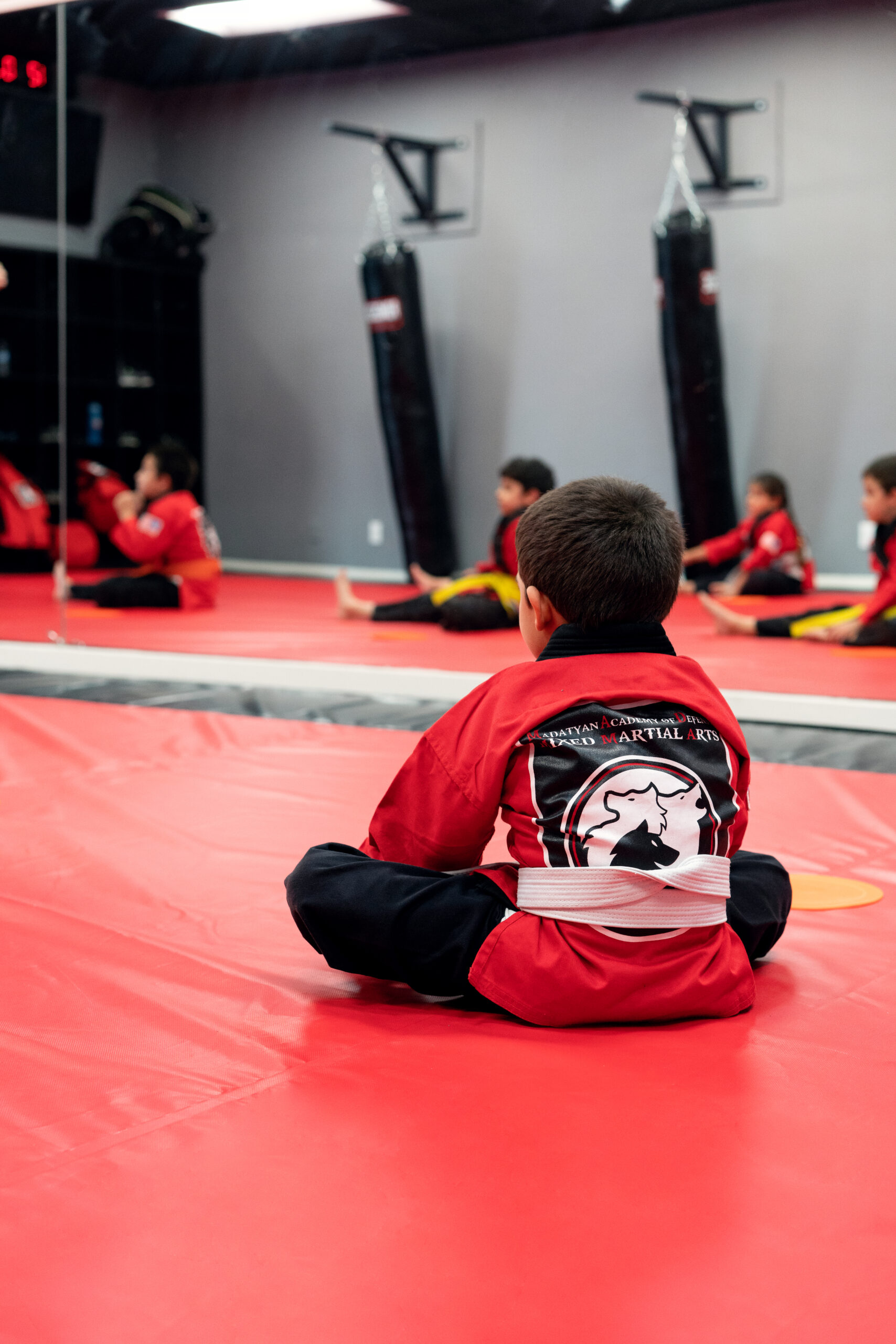 A student sits preparing to take part in mixed martial arts training.
