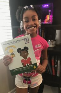 Black little girl holding Lil's Science Experiment book