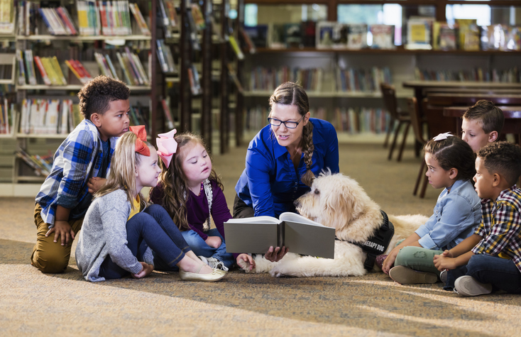 A multi-ethnic group of six boys and girls sitting on the floor of a library, reading with a therapy dog, a goldendoodle. The dog handler is a mature woman in her 50s who is smiling holding a book and reading aloud. The girl 3rd from the left has down syndrome.