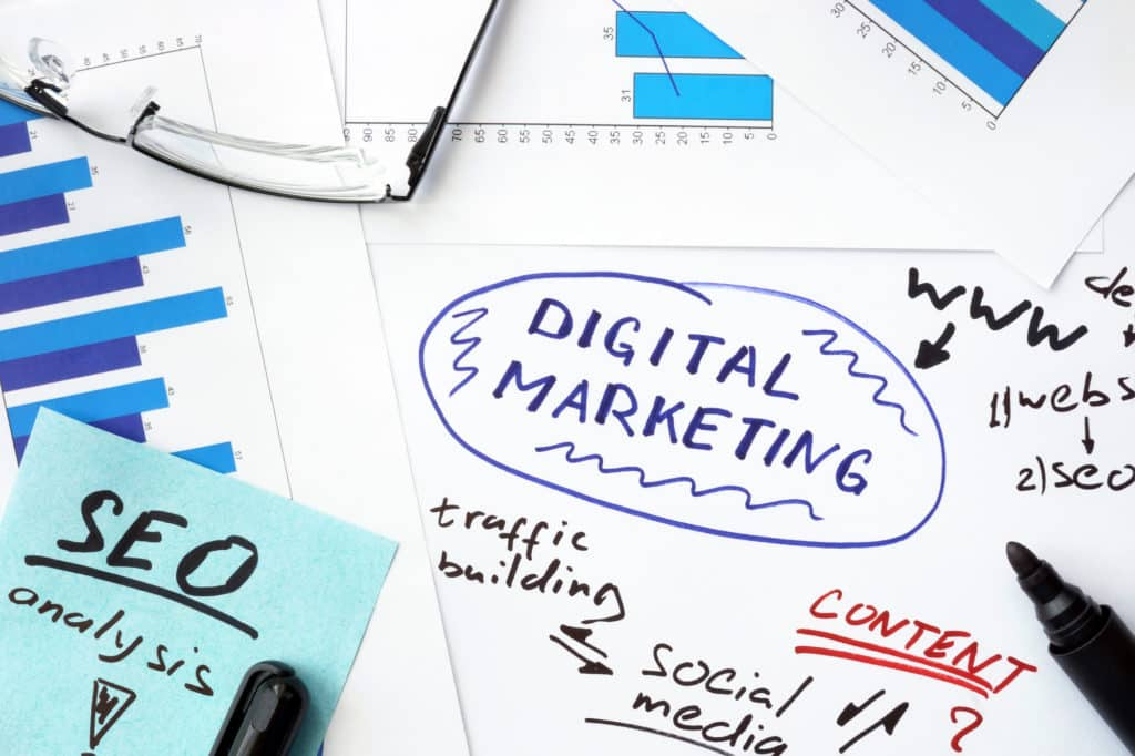Papers with graphs and digital marketing concept.