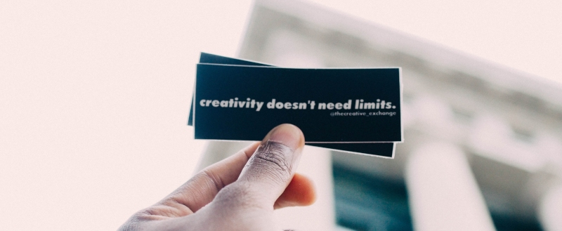 hand holds up small card reading 'creativity doesn't need limits'