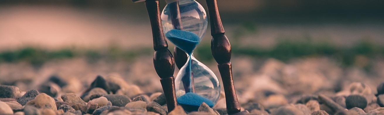 hour glass sand timer sitting on rocks