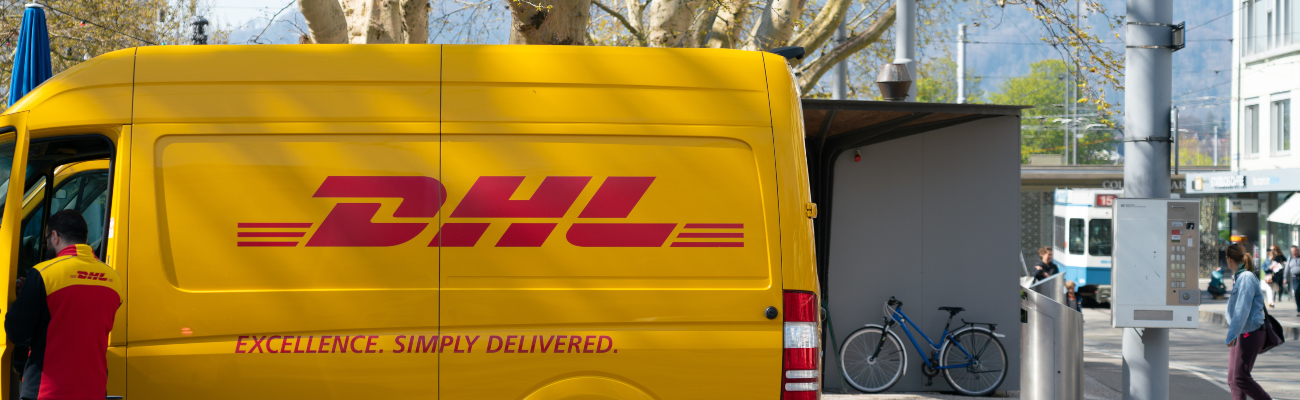 DHL delivery van parked with delivery man standing outside the van with open door.