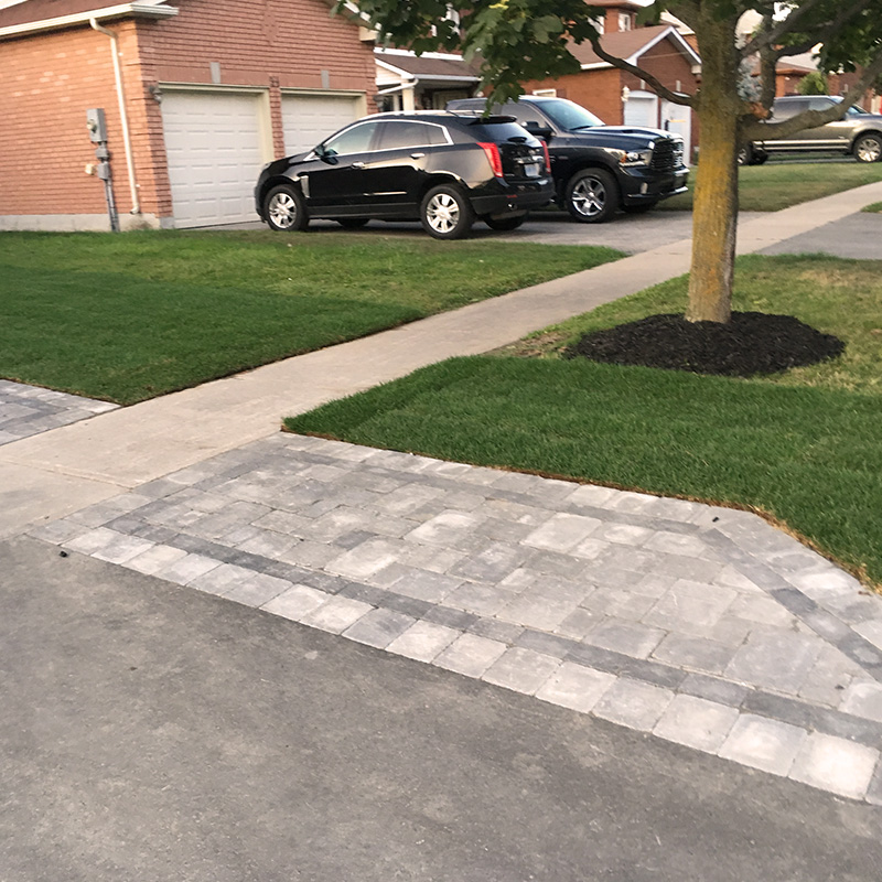 Stonework walkway beside driveway