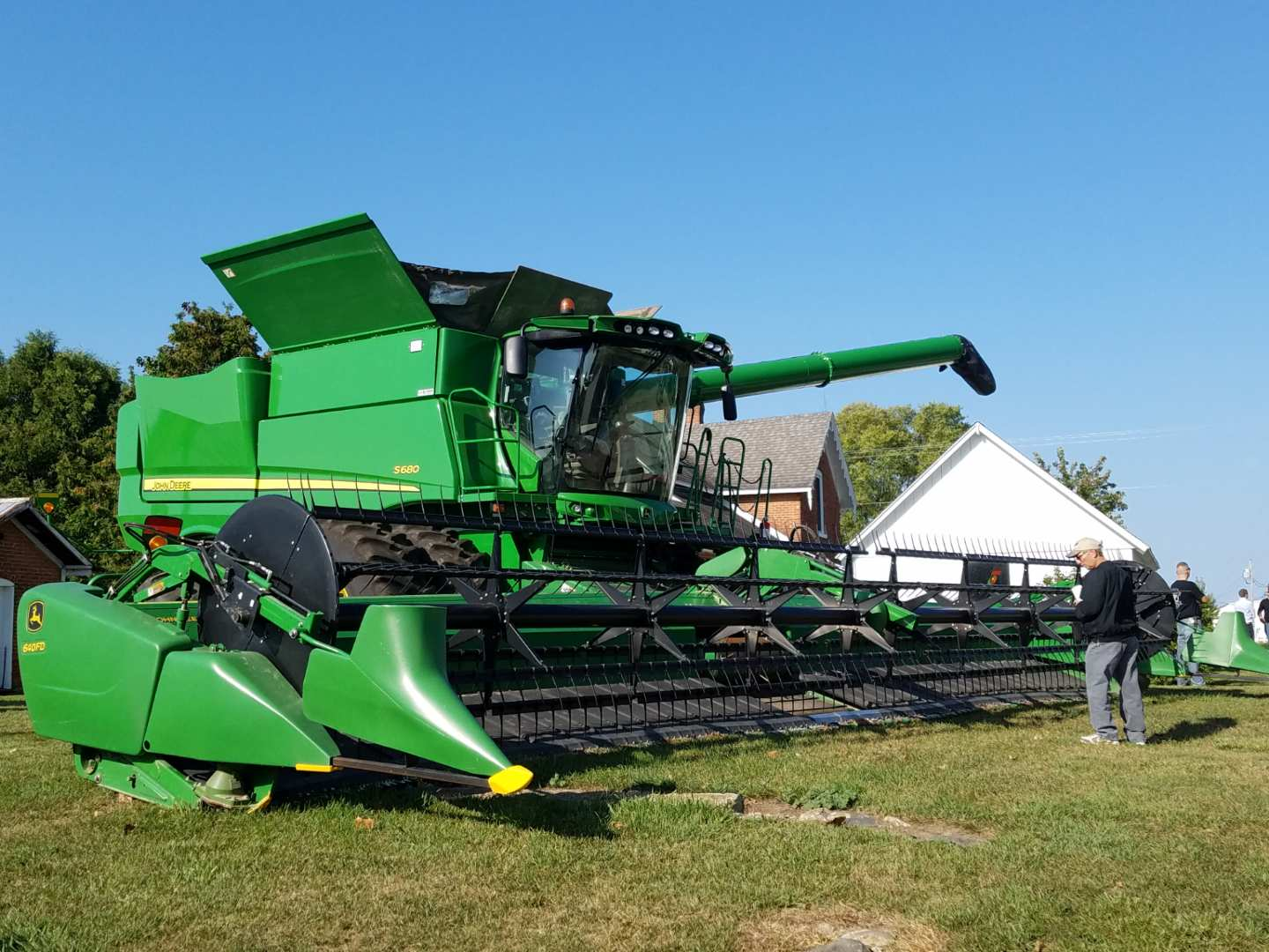 man standing in front of large farm machine.