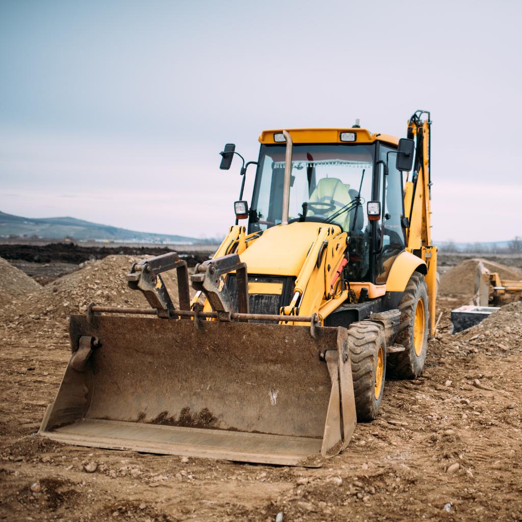 Backhoe on a dirt dig site.