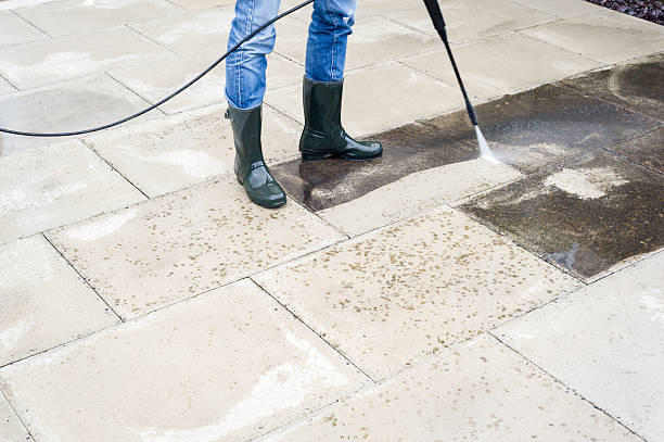 Male in worn jeans and wellies using a pressure washer to clean a paved residential patio from dirt, algae and lichen. While the algae is quite easy to remove, a second pass is needed to get rid of the darker spots of lichen.