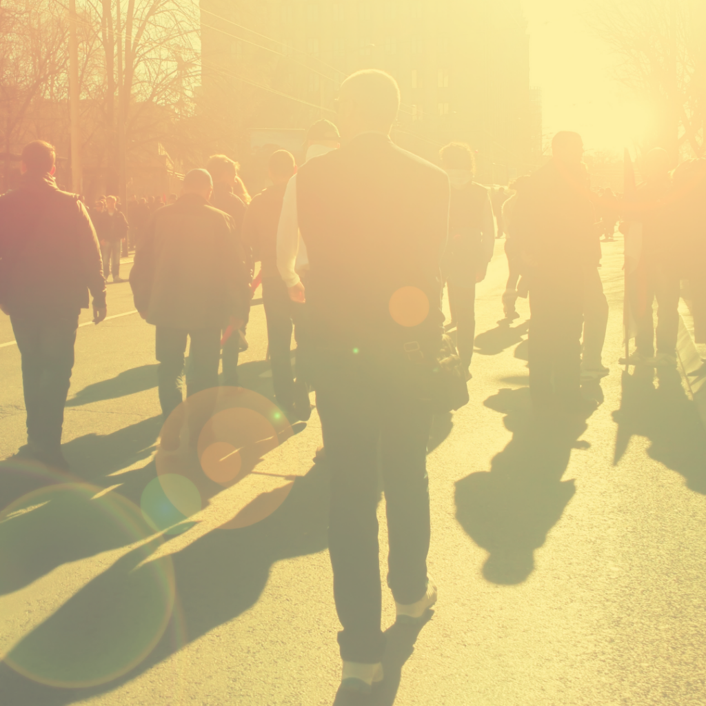 group of people walking away from the camera while the sun shines in front of them. yellow fade over photo.