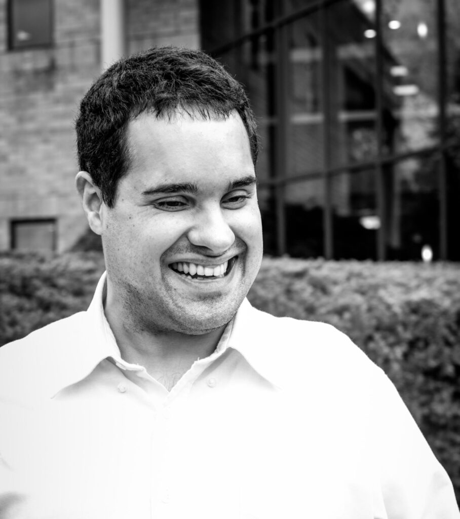 black and white photo of blaise wearing a button up, smiling