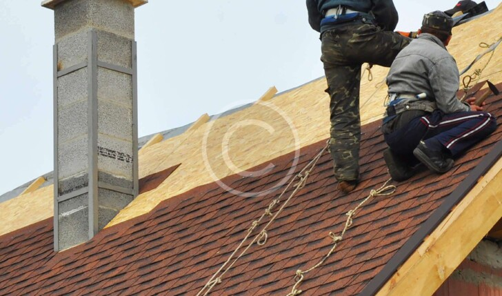 Workers on Roof as they lay down red shingles