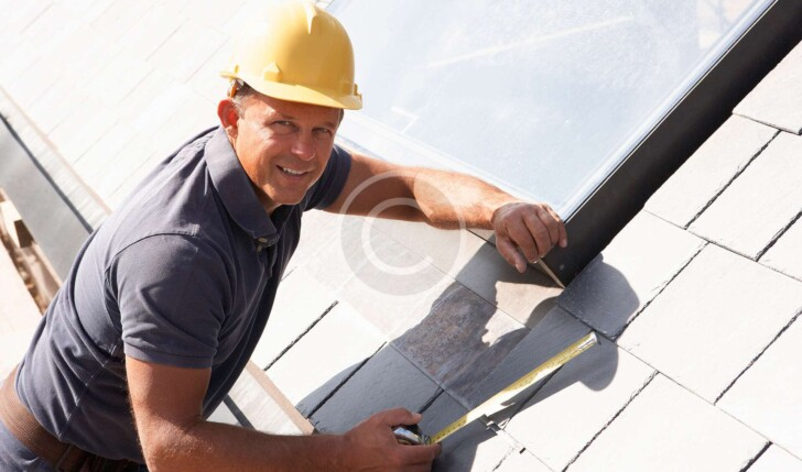 Man on Roof with measuring tools