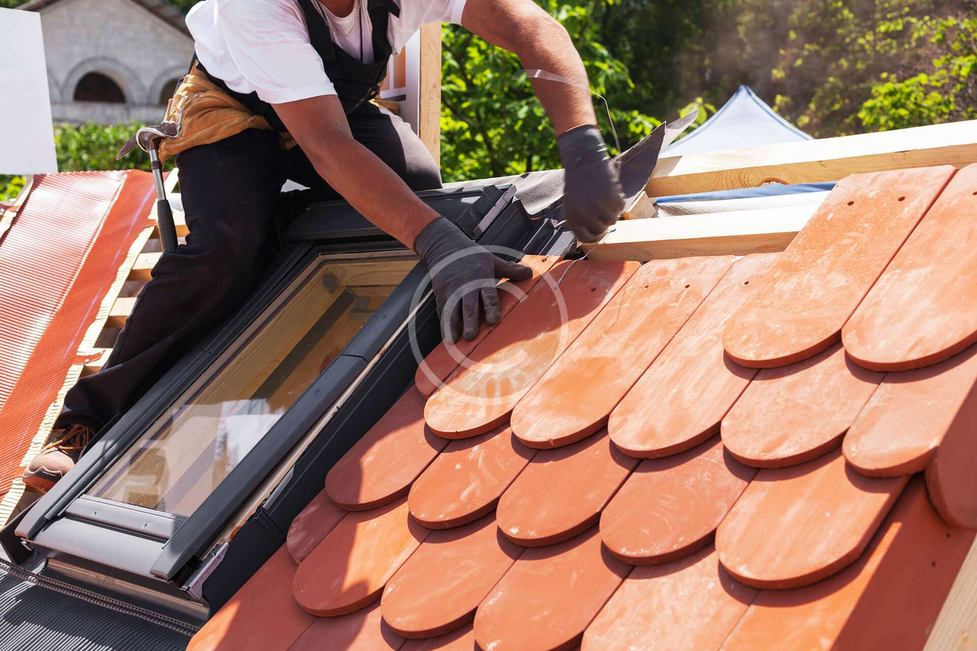 Man putting red shingles in place