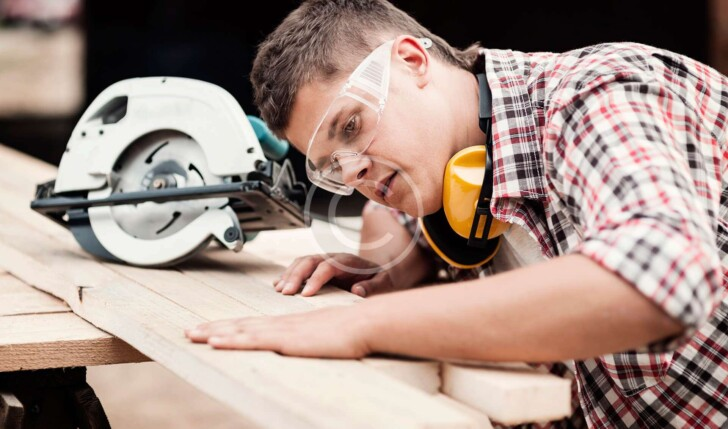 Worker touching wooden board before sawing