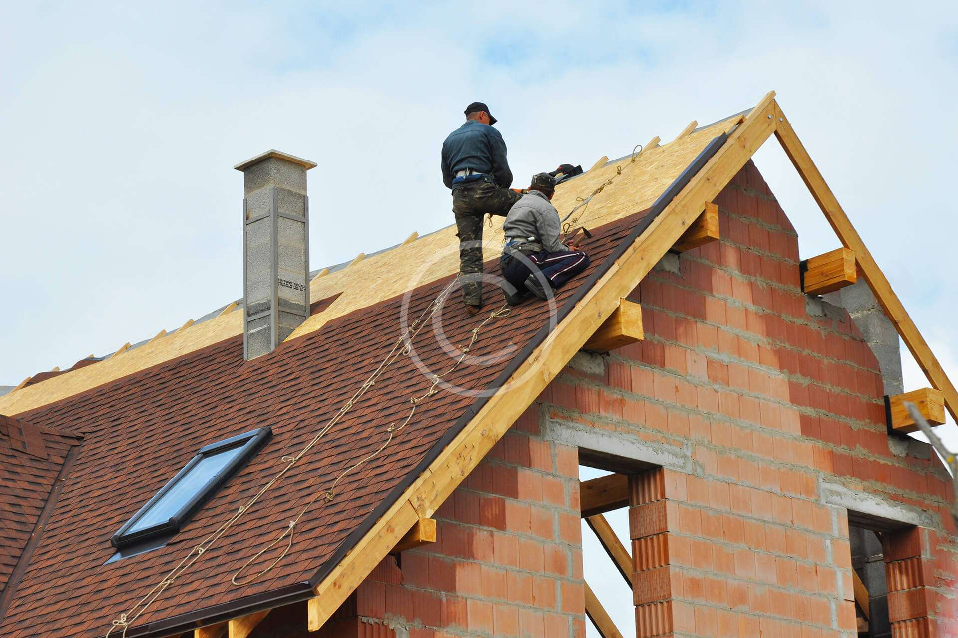 Workers standing on roof while laying down shingles