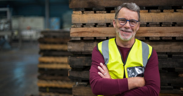 Male factory worker standing with arms crossed