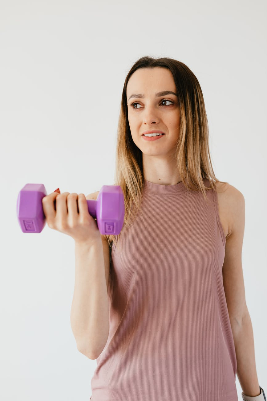 happy young sportswoman doing exercise with dumbbell