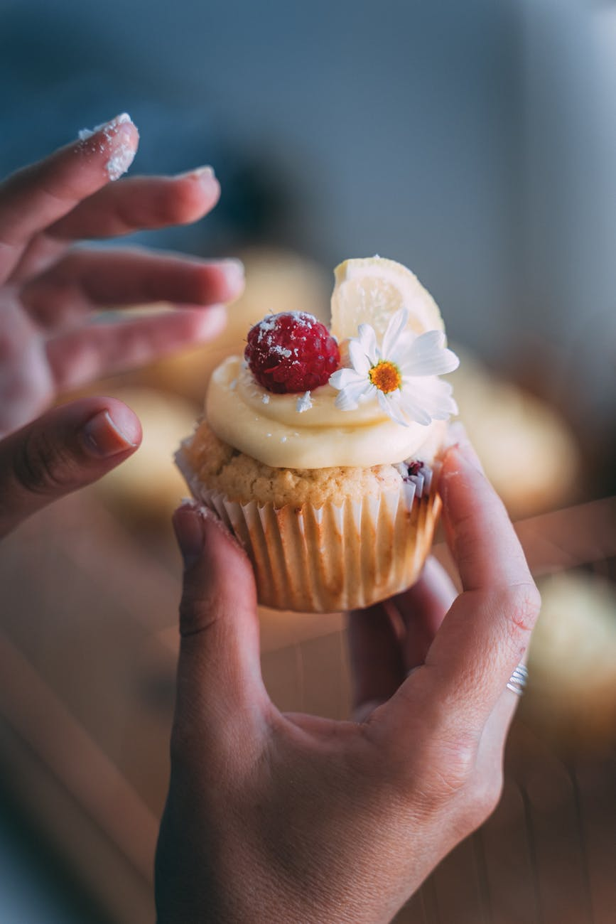 person holding cupcake with white icing