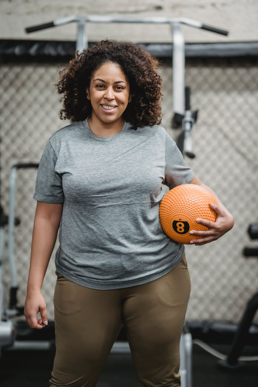 happy young ethnic woman with medicine ball smiling in modern gym