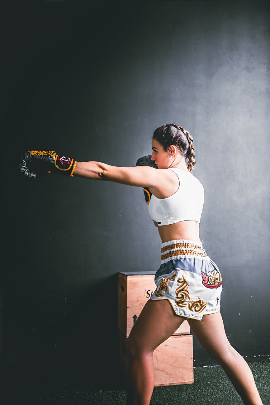 young strong woman in trendy sporty shorts boxing
