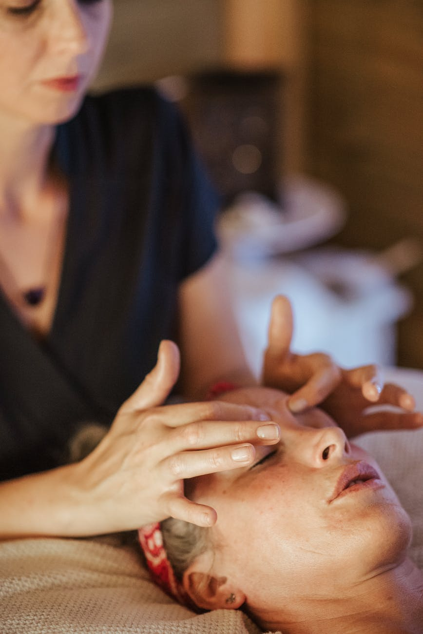 woman with closed eyes getting massage in salon
