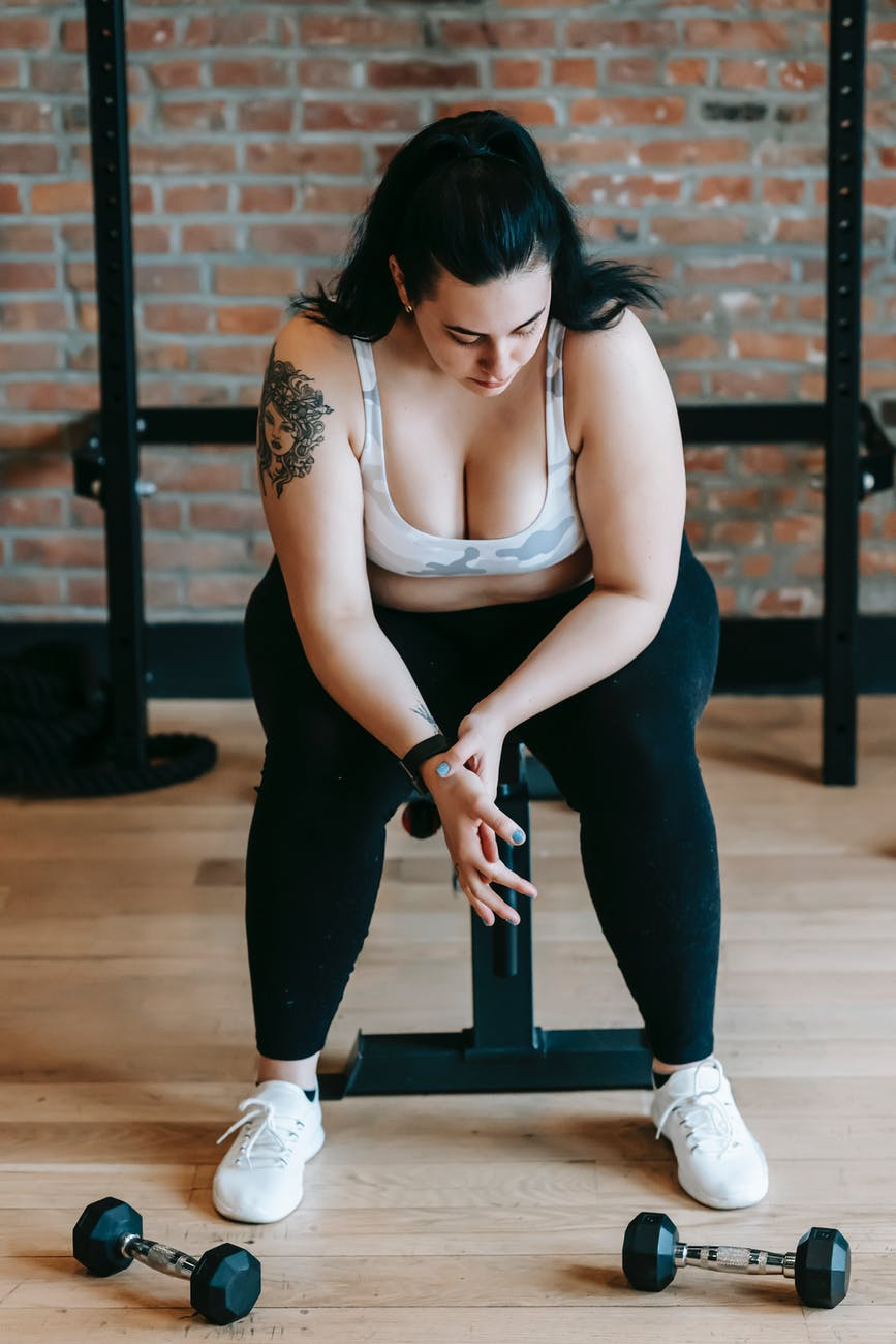 overweight female sitting on bench after exercise with dumbbells
