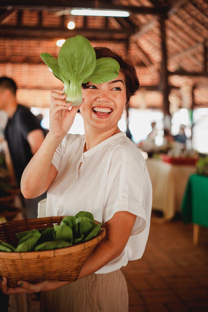 happy ethnic woman with salad leaf