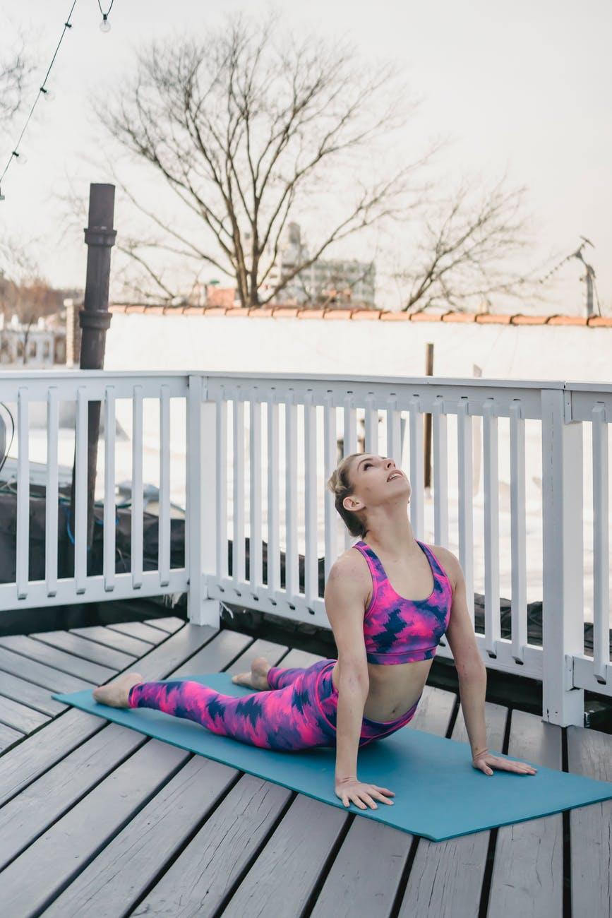 flexible young lady doing bhujangasana yoga pose on terrace in morning