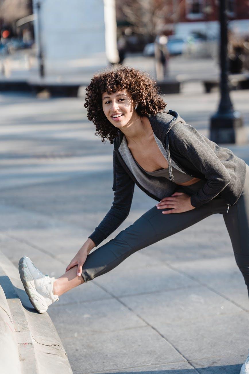 happy ethnic woman in activewear exercising on street