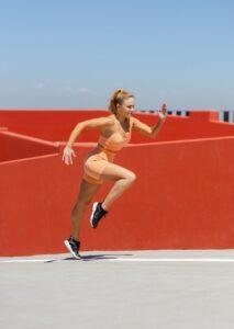 woman in orange sports wear running