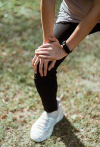 crop sportswoman stretching legs on green lawn