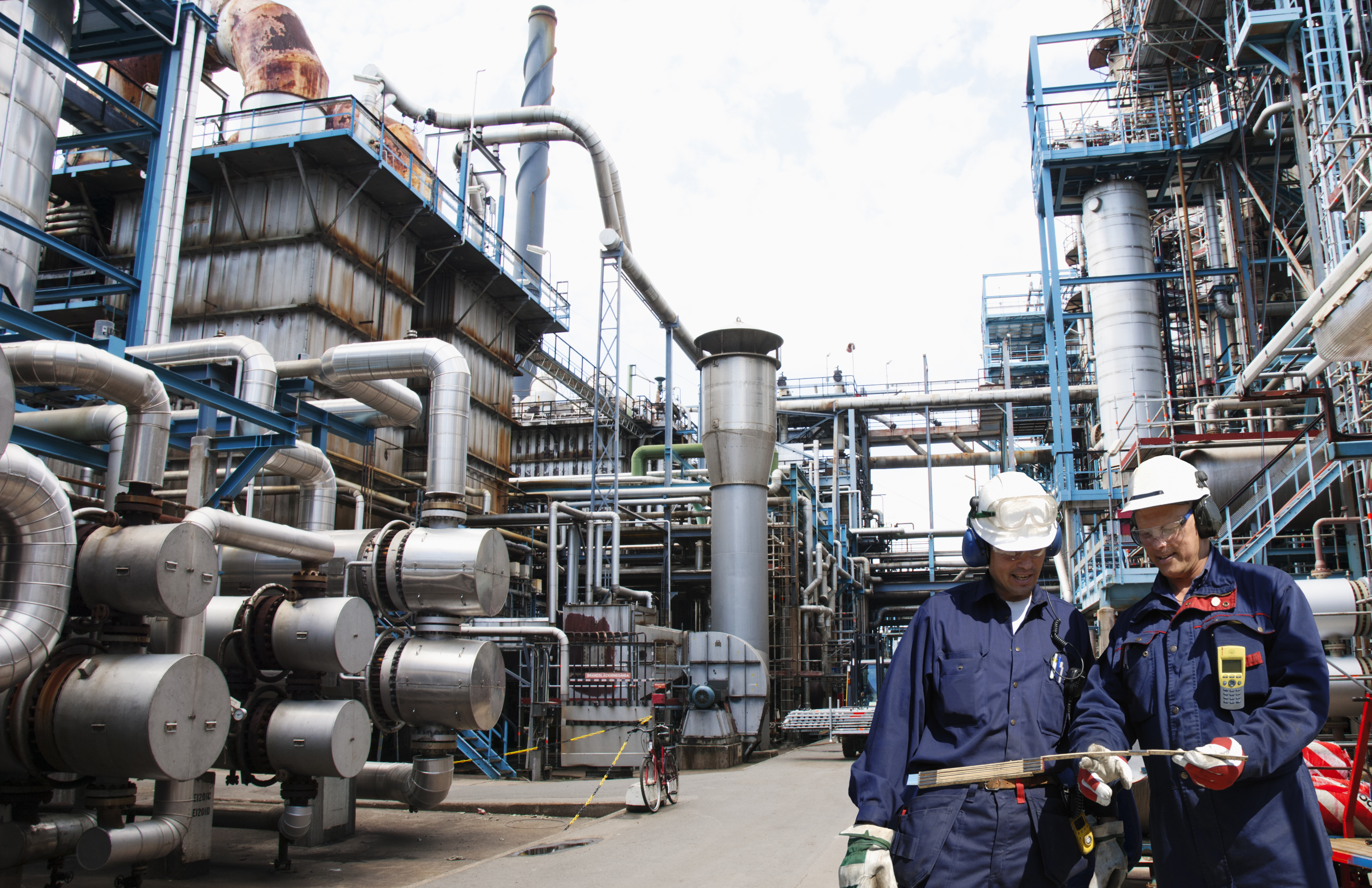 two oil and gas workers inside large refinery, oil and gas.
