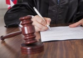 Close-up Of Male Judge Writing On Paper In Courtroom
