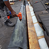 A man drilling down materials in the process of a roofing job and roof repair