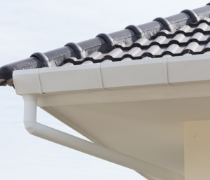The corner of a tile roof that has a newly installed gutter and spouting system